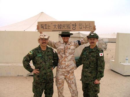 プラカードを掲げる韓国軍兵士と自衛隊員が記念撮影